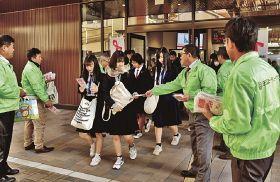 高校生らに啓発品を手渡す、田辺ロータリークラブのメンバー(21日、和歌山県田辺市湊で)